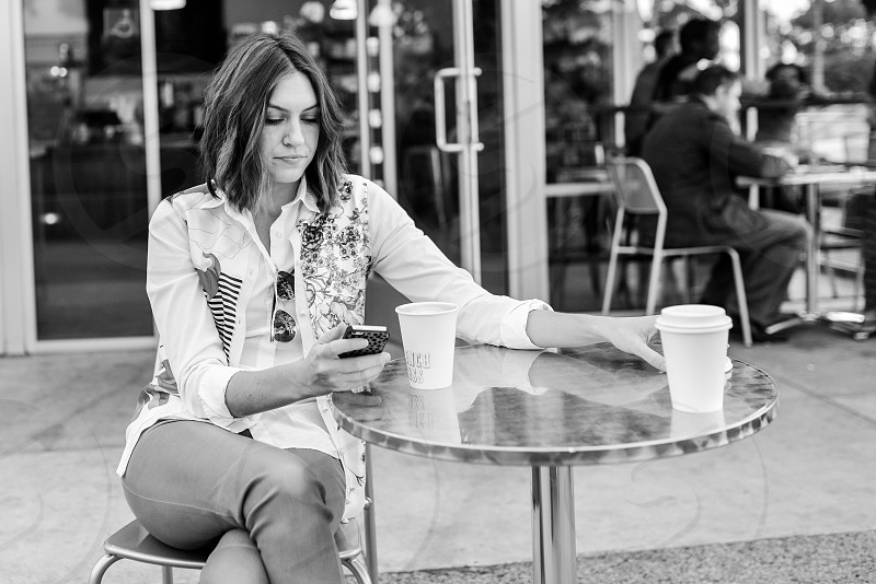 young woman girl texting phone coffee shop cafe b/w photo