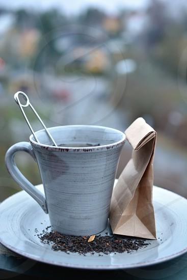 safety pin in grey ceramic mug photo
