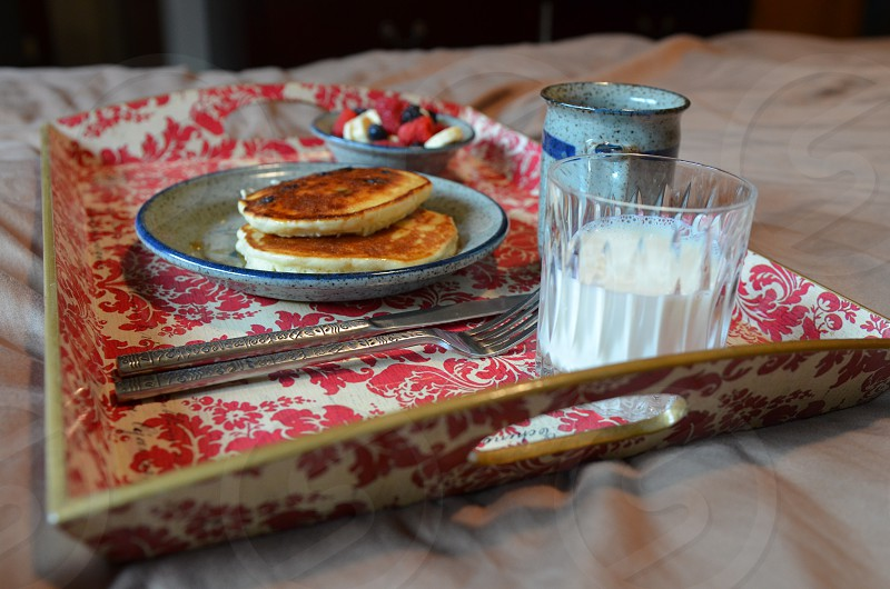 Breakfast in bed with pancakes berries milk & coffee on red & white floral tray photo