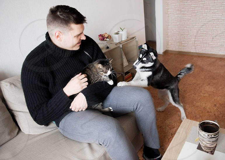 A young man with their pets resting at home photo