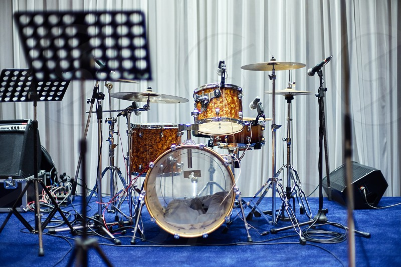 Classic vintage of empty drum set on the blue floor for music band with note song sheet stand in foreground setup for party night photo
