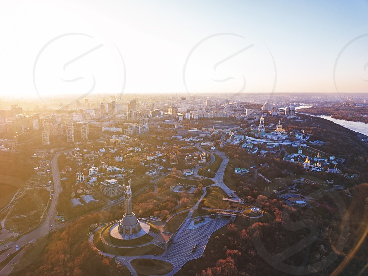 Panoramic photography from the drone bird's eye view to historical famous places in Kiev Dnieper River and to the left bank of city with modern buildings at sunset in the summer. photo
