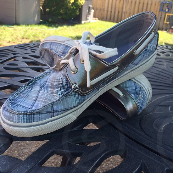 Blue plaid shoes; silver shoes; summer shoes; shoestrings; outdoor table photo