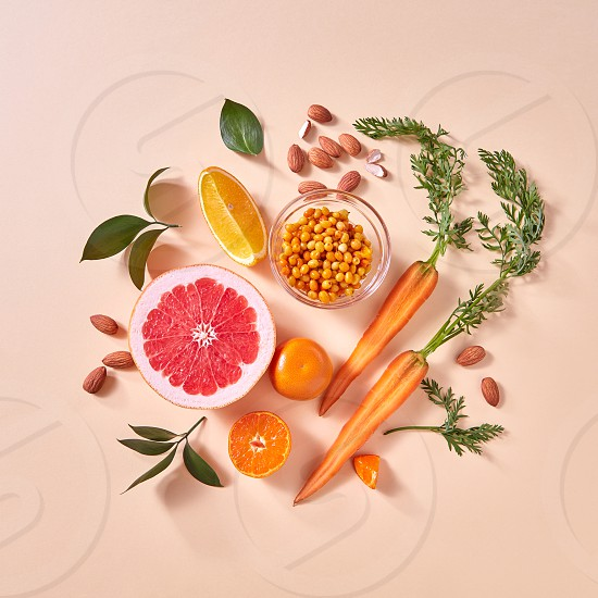 Healthy vegetarian food - orange organic vegetables and fruits on a paper background. Top view. Concept of organic natural vegetarian food. photo
