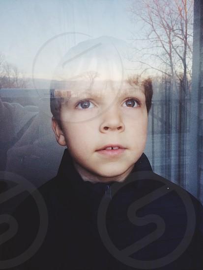 boy wearing black zip up jacket standing outdoors photo