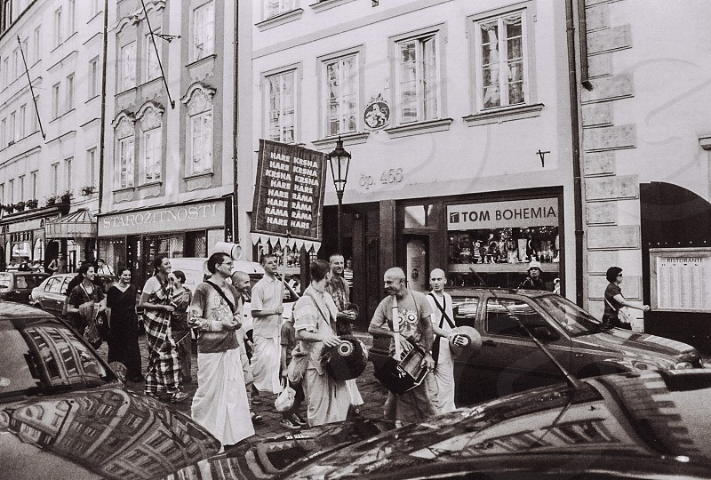 people on street by store with cars in greyscale photo