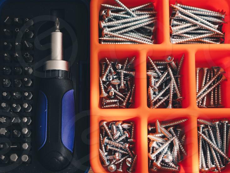 grey metal screws on orange organizer box photo