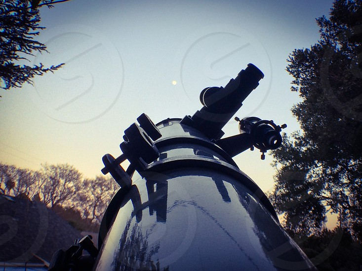 large black cylindrical telescope pointed at the moon photo