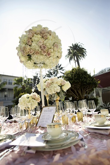 Tall pink white cream bouquet flower centerpieces with beads and crystals on a tablecloth with silverware stemware flatware china teacups plates goblets napkins with a palm tree and hedges in the background. photo