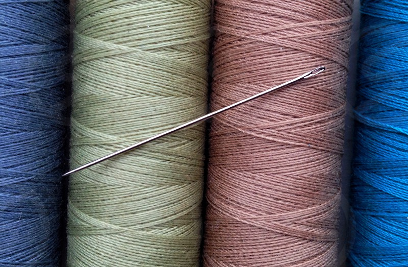 silver needle on white brown and blue nylon threads photo