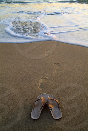 Flip flos on the beach with footprints leading to the water. photo