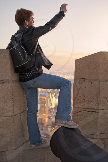 A woman takes a selfie from Santa Barbara Castle  in Alicante Spain photo
