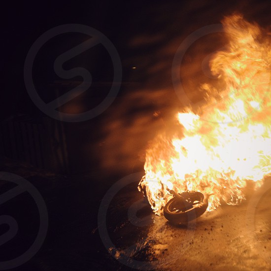 Burning motobike on a side of suburban road. Night fire moto crash wheel ride danger documentary accident situation. Mobilography. Saratov Russia 2015 photo