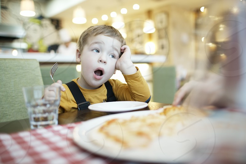 Young boy yawning as he waits to be fed sitting at the dining table with an empty plate in front of him photo