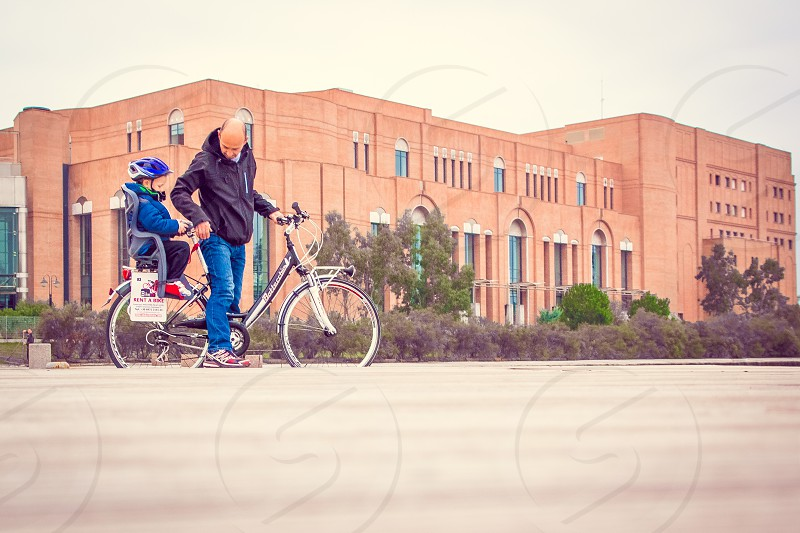 man in black jacket and blue jeans riding bicycle with child on bike seat trailer photo