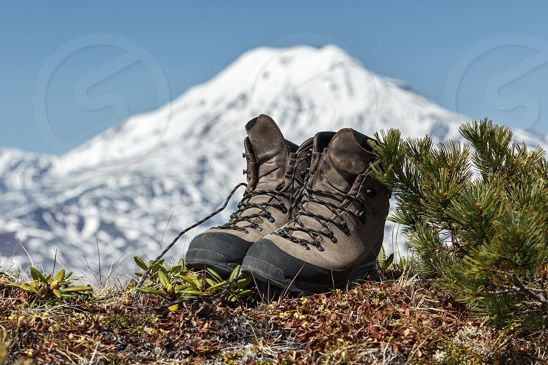 Pair of old tourist boots on background volcano on Kamchatka Peninsula. Russia Far East. photo
