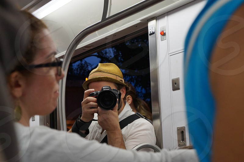 man in white polo shirt holding black nikon dslr camera and taking pictures of woman in white long sleeved shirt photo