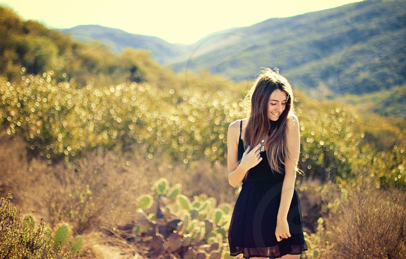 woman with long hair in field near hills in black semi-sheer layered camisole dress smiling in daytime photo