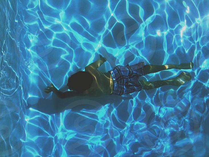boy swimming in pool underwater photo