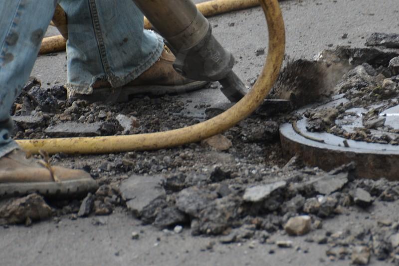 Jackhammer man manhole asphalt photo