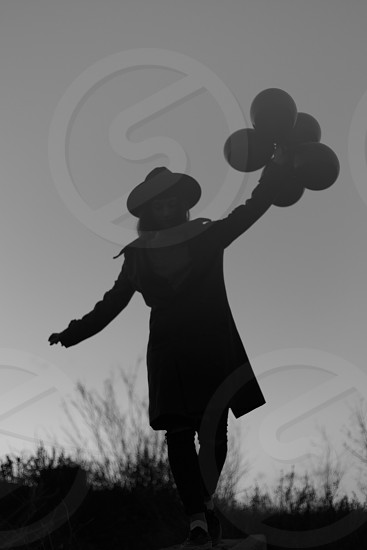low angle grayscale photo of woman wearing hat with balloons photo