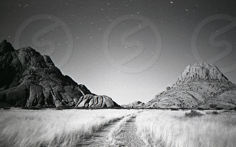 grayscale poster of mountains and grass photo