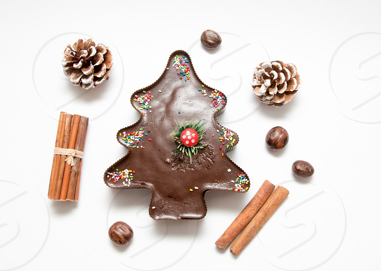 Composition Of Christmas Tree Chocolate Muffin Cupcake Pine Cones Nuts And Cinnamon Isolated On White Background photo