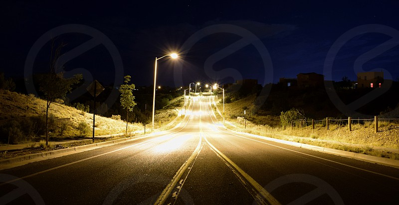 Looking down the centerline of an empty road late at night. Light from the streetlamps pooling on the asphalt. photo