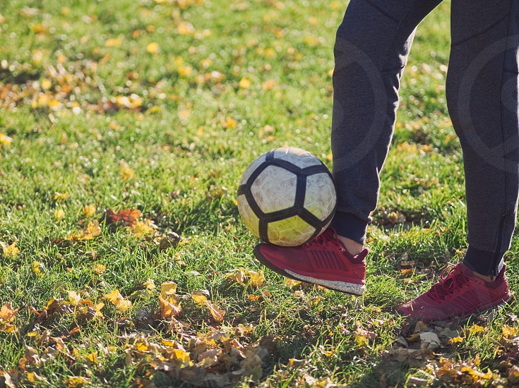 Soccer Player Practicing with Football in the Park on a Sunny Autumn Day photo