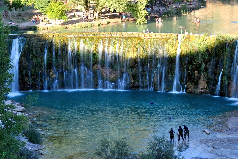 people enjoying the water in a waterfall reservoir into a lagoon photo