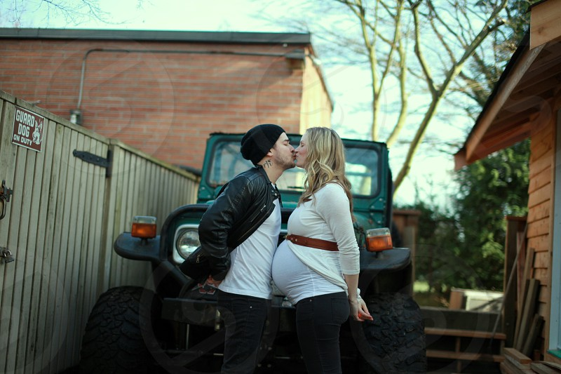 pregnant woman kissing man wearing white shirt and black jacket standing in front of black car photo