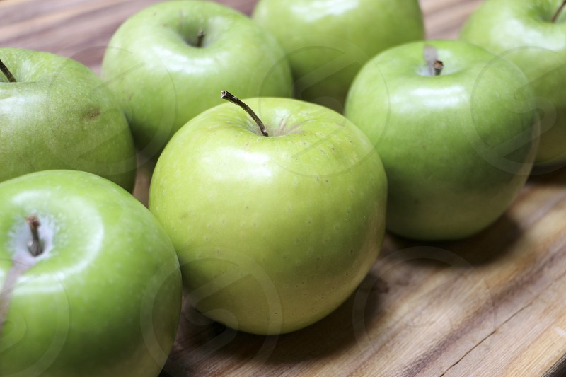 Green apples on a cutting board photo