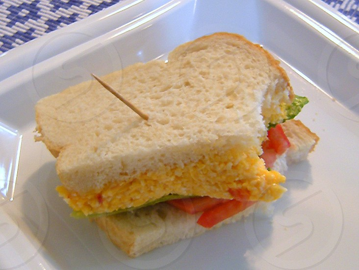 Half a pimento cheese sandwich with tomatoes on white photo