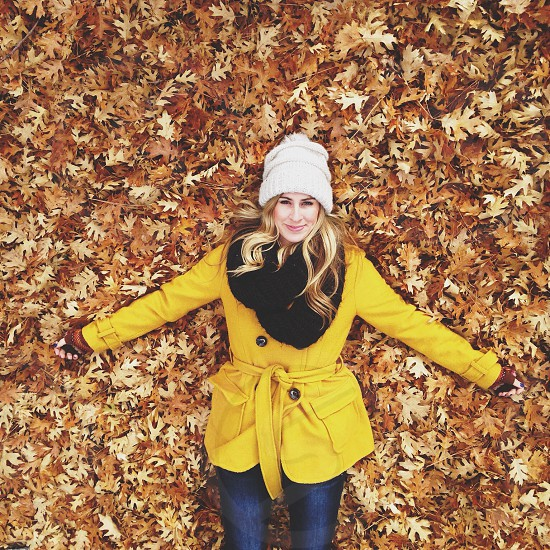 woman wearing yellow coat with black neck trim and yellow belt laying in fall leaves photo