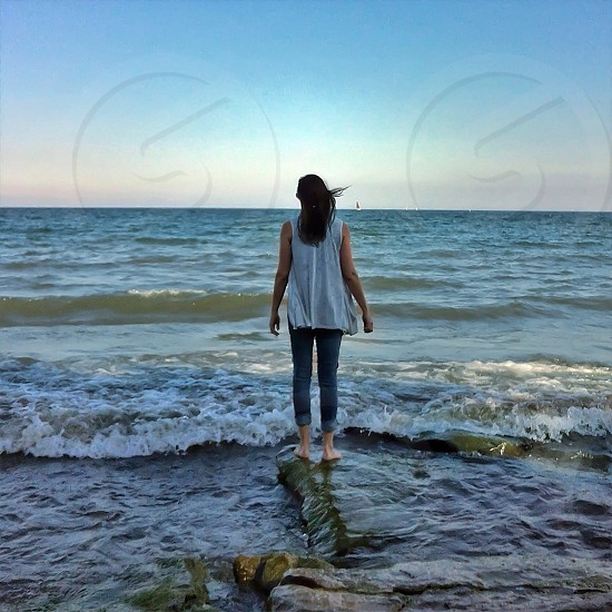 woman standing on shore in waves photo