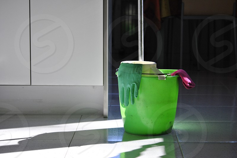 green plastic bucket with green glove beside white painted wall photo