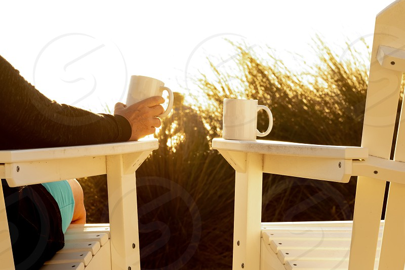 Two chairs one female two coffee cups beach grass at sunrise. photo