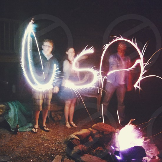 several person holding sparklers forming USA light streak photography during nighttime photo