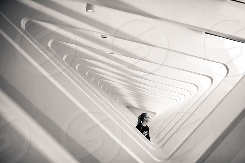 A woman stands amidst an architectural structure.  Concentric tunnel triangles shapes contrast negative space museum lights windows supports beams joists. photo