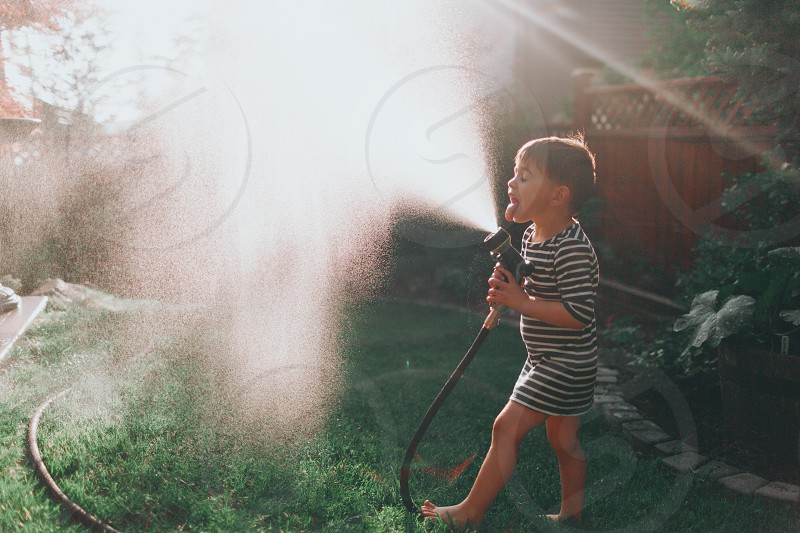 A boy keeping cool in the hose on a summer day. photo
