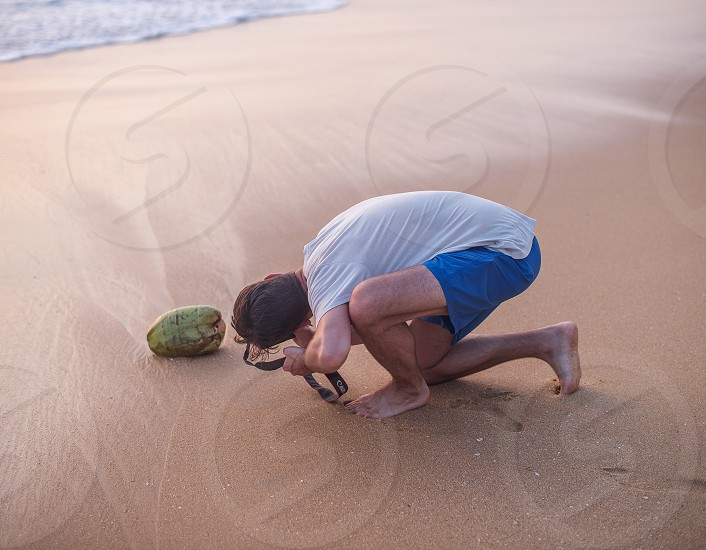 The photographer looking through his lens at the beach coconut. photo
