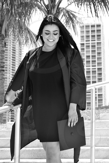 Grad graduation celebrating final finale sexy female happy glad eyes beauty bnw cap and gown gown smile joy accomplishment  photo
