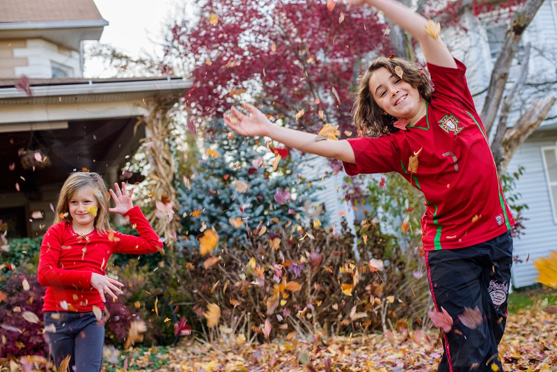 2 girls in red shirts playing with dried leaves at daytime photo
