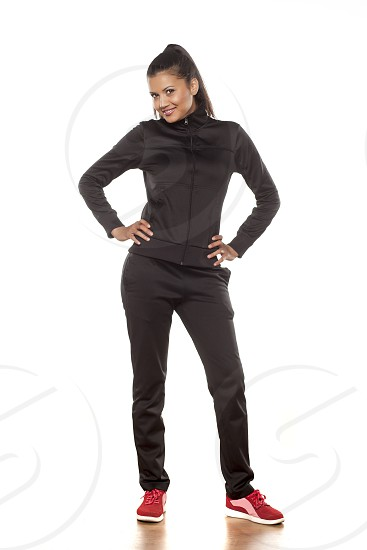 young pretty woman in tracksuits posing in the studio photo