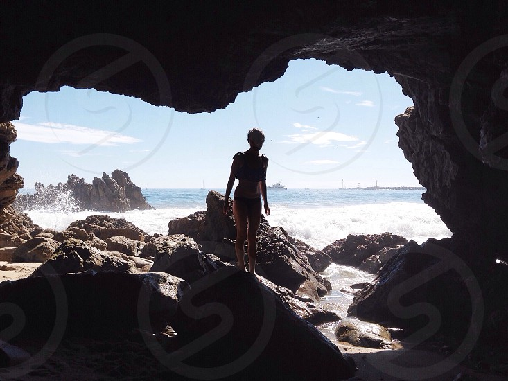 woman standing at the entrance of a cave during daytime photo