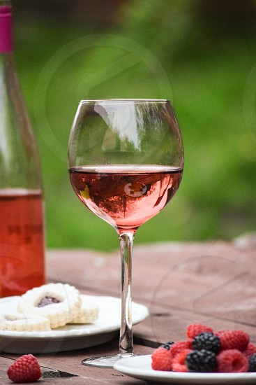 shallow focus photography of a glass of red wine during daytime photo