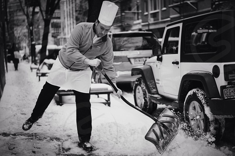grayscale photo of man holding snow shovel photo