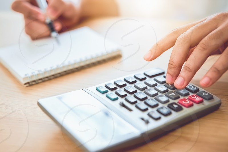 Woman holding and press calculator to calculate income expenses and plans for spending money on home office. photo