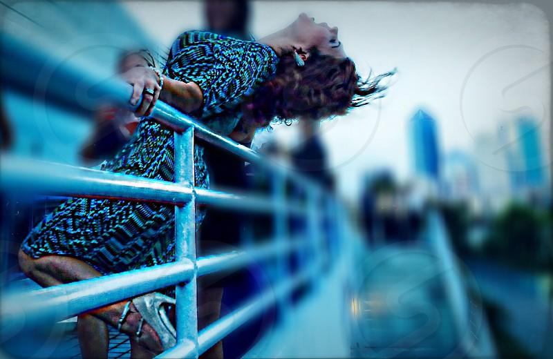 woman leaning on metal railings photo
