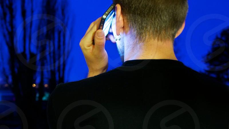 man in black shirt on lit smartphone at night photo
